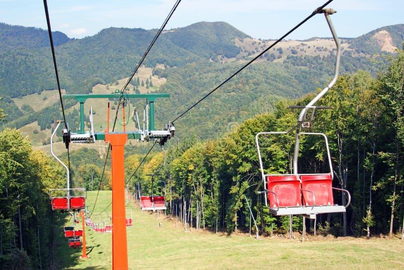 Ski chair lift for ski trail. Ski chair lift over green forest for ski trail stock photo