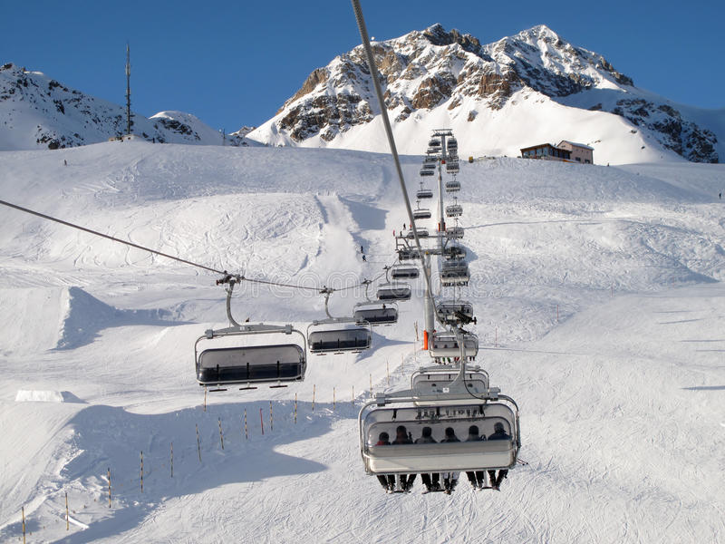Ski chair-lift with skiers. (Switzerland royalty free stock image