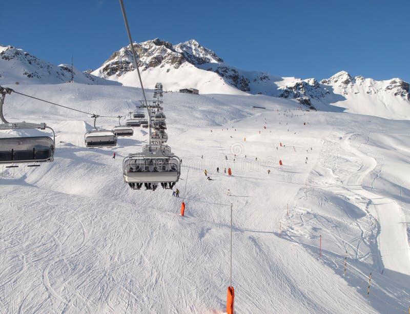 Ski chair-lift with skiers. (Switzerland royalty free stock photo