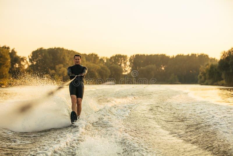 Ski d'eau masculin derrière un bateau sur le lac photos libres de droits
