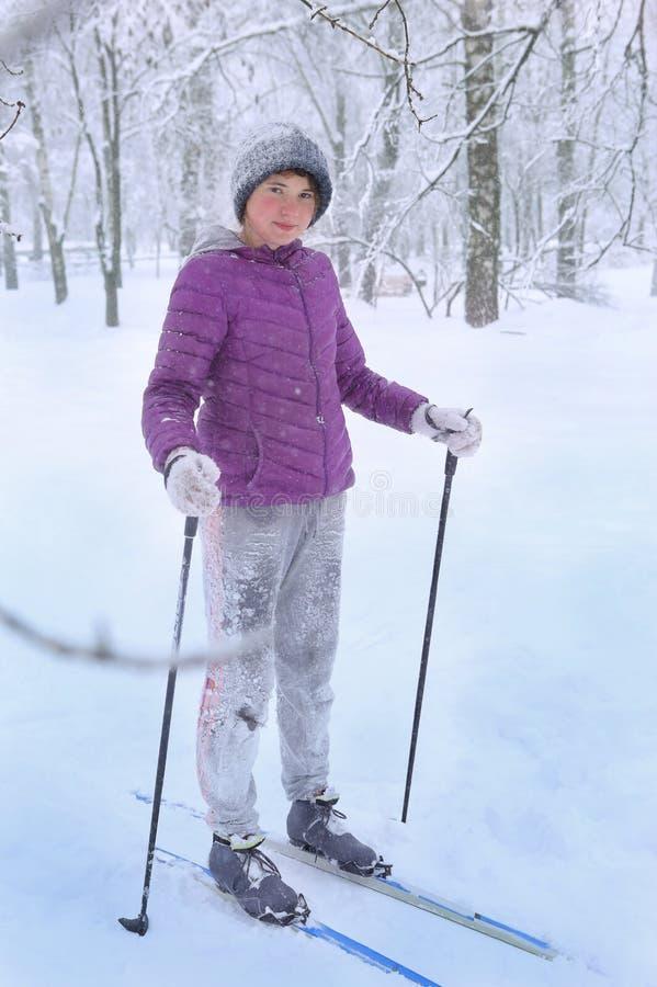 Ski de fille d'adolescent en parc dans la veste tricotée d'aube de chapeau avec le ski photographie stock libre de droits