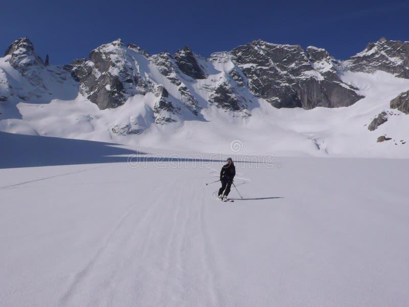 Ski de skieur de Backcountry sur un glacier pittoresque dans les Alpes de la Suisse avec un grand paysage de montagne derrière photos libres de droits