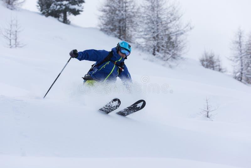 Ski de skieur de Freeride dans la neige profonde de poudre photo stock