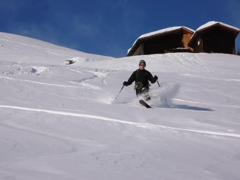 Ski de teelemark d'homme dans le backcountry suisse en hiver profond et poudre fraîche un beau jour photo stock
