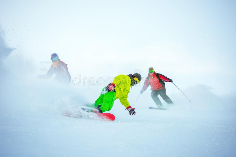 Ski downhill concept with group of snowboarders royalty free stock image
