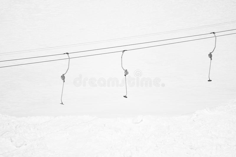 Ski drag lift isolated in snowcapped mountains, texture background, ski concept in black and white. Ski drag lift isolated in snowcapped mountains, texture stock images