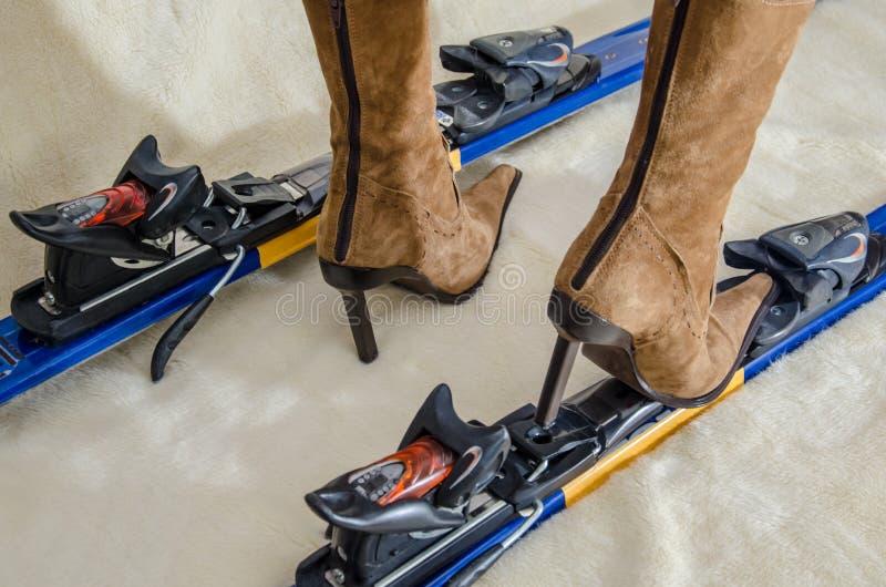 18 02 007 Ski en glamour Het meisje in schoenen met hoge hielen probeert om op skis op te staan stock foto