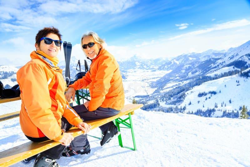 Ski fahrende ältere Paare, die einen Bruch haben lizenzfreie stockbilder