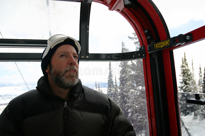 Ski Guy Goldola Ride. A middle-aged man inside a gondola takes a ride up the mountain to ski. He has a beard and a mustache, black coat and is wearing ski royalty free stock images