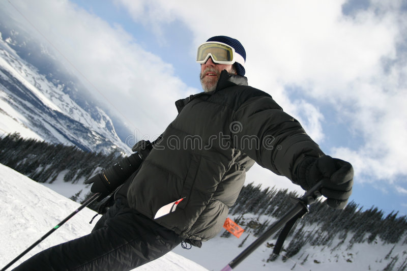 Ski Guy on Slope. Middle aged guy with yellow ski goggles and camera on a ski slope. He has a camera with long lens , black clothes and a blue knit hat. He is royalty free stock photography