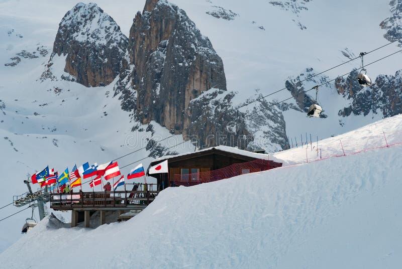 Ski hut chalet mountain peak restaurant at ski slope with national flags sun royalty free stock photos