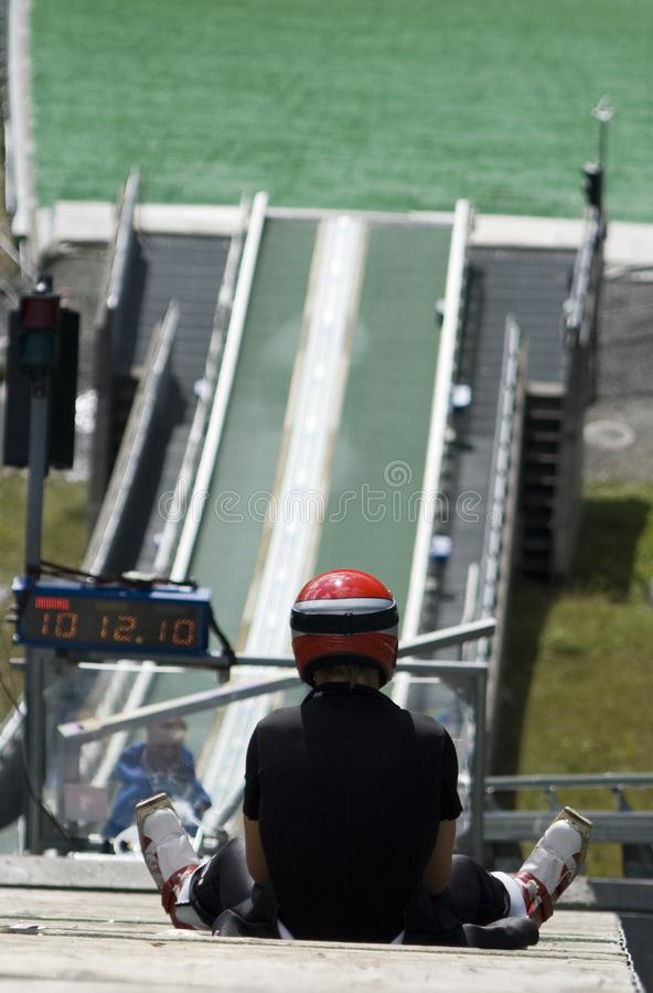 Ski jumper. Summer training session for a ski jumper. He sits on the bar and get s ready to jump stock images