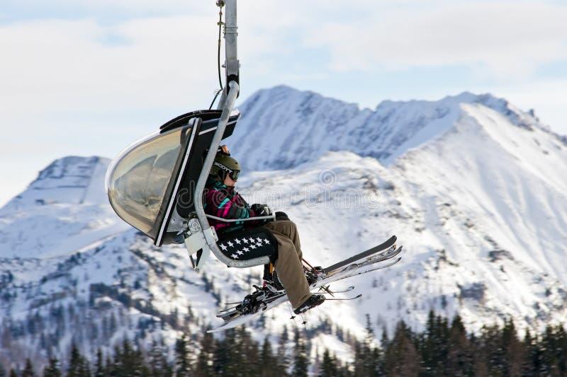 Ski lift. FLACHAU, AUSTRIA - DEC 27: Skiiers on a ski lift to a piste in Flachau, Austria on Dec 27, 2012. These pistes are part of the Ski Armada network, the stock photos