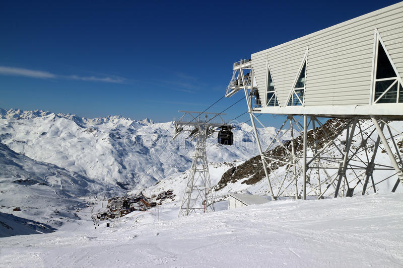 Ski lift in Alps. Ski lift in high mountains, with slopes going down to a village, on a sunny winter day royalty free stock image