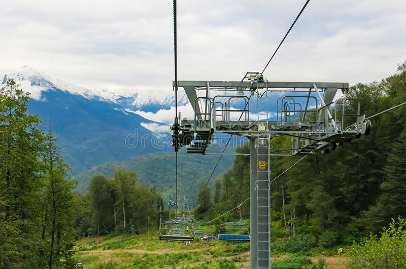 Ski lift. On a background of snow-capped peaks royalty free stock photos