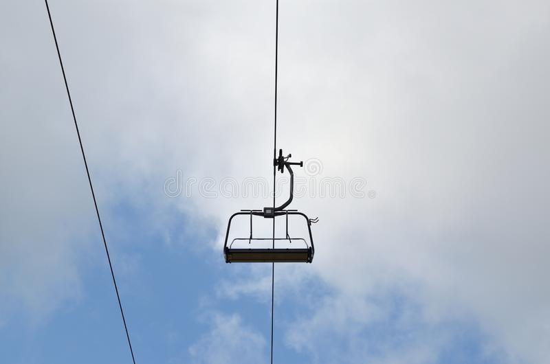 Ski lift chair. Empty ski lift chair against cloudy sky royalty free stock image