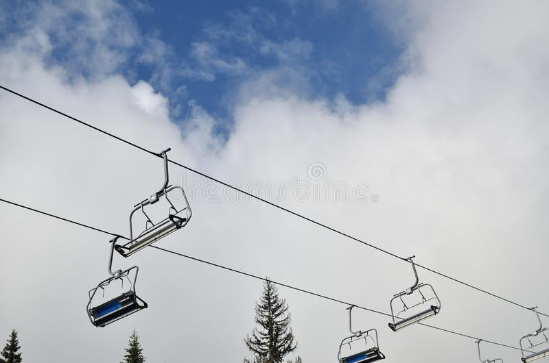 Ski lift chairs. With no one on them - against cloudy sky royalty free stock images