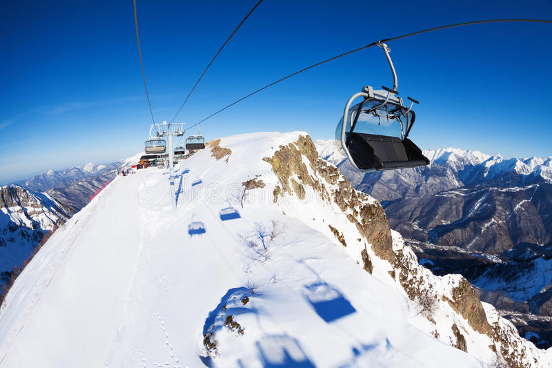 Ski lift with chairs, ropeway over mountain range stock images