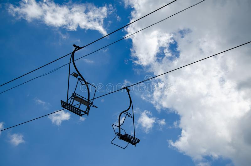 Ski lift chairs. With no one on them - against cloudy sky royalty free stock photography