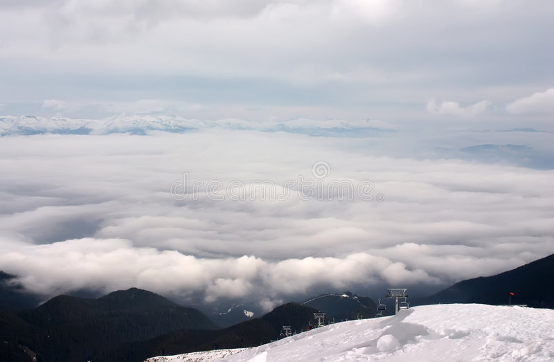 Ski lift with clouds. Ski lift in clouds with forest and snow royalty free stock photos