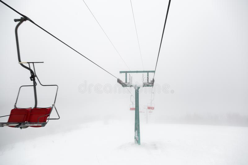 Ski-lift in fog. On a winter day royalty free stock photo