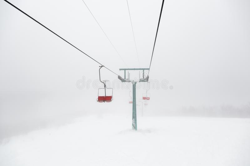 Ski-lift in fog. On a winter day stock images