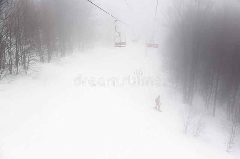 Ski-lift in fog. On a winter day stock photos