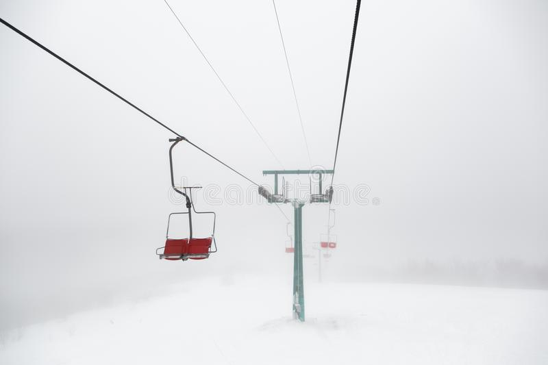 Ski-lift in fog. On a winter day stock photography