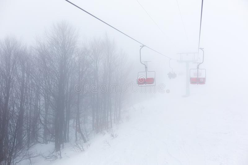 Ski-lift in fog. On a winter day royalty free stock images