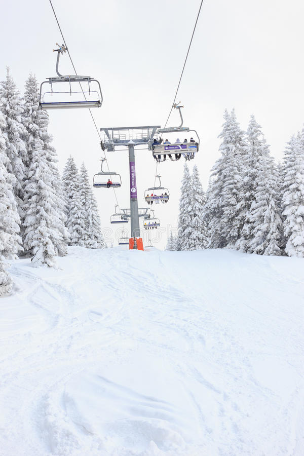 Ski lift in mountain with skies and snowboards people. Ski lift in mountain with paths of skies and snowboards. Skiers in a chair lift above the downhills royalty free stock photos