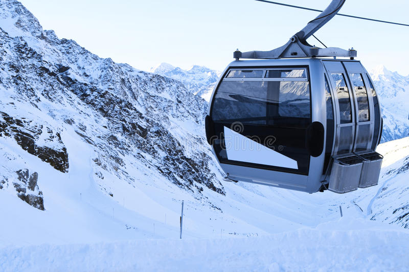 Ski lift in mountains. Ski lift chairs on bright winter day in Alp mountains stock photo
