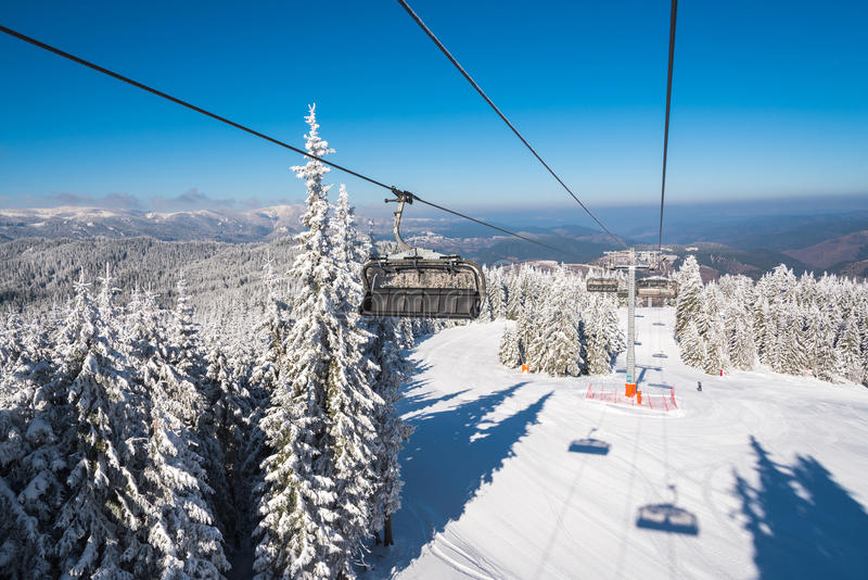 Ski lift with seats going over the mountain over ski tracks stock photo