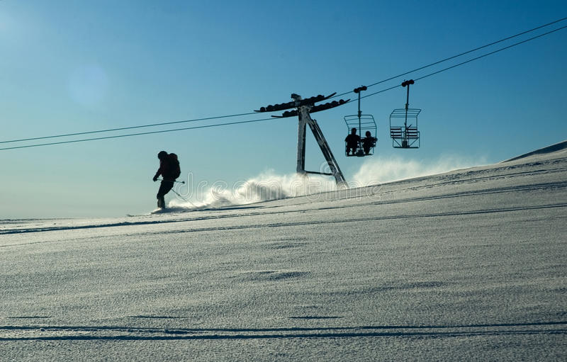 Ski lift and skiing in the powder snow stock image