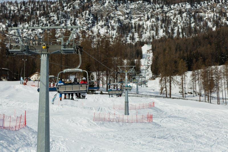 Ski Lifts moderno com os esquiadores em cumes italianos das dolomites no dia de inverno com neve fotos de stock royalty free