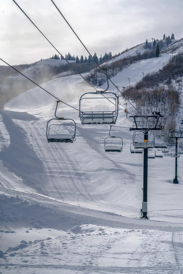 Ski lifts overlooking sunlit snow covered mountain. Ski lifts in Park City, Utah overlooking a snow covered mountain on a ski resort. Sunlight beams down on royalty free stock image