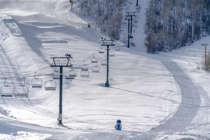 Ski lifts and snow cannons agaist sunlit snow. Empty ski lifts and bright snow cannons of a ski resort against sunlit snow covered mountain slope in Park City royalty free stock images