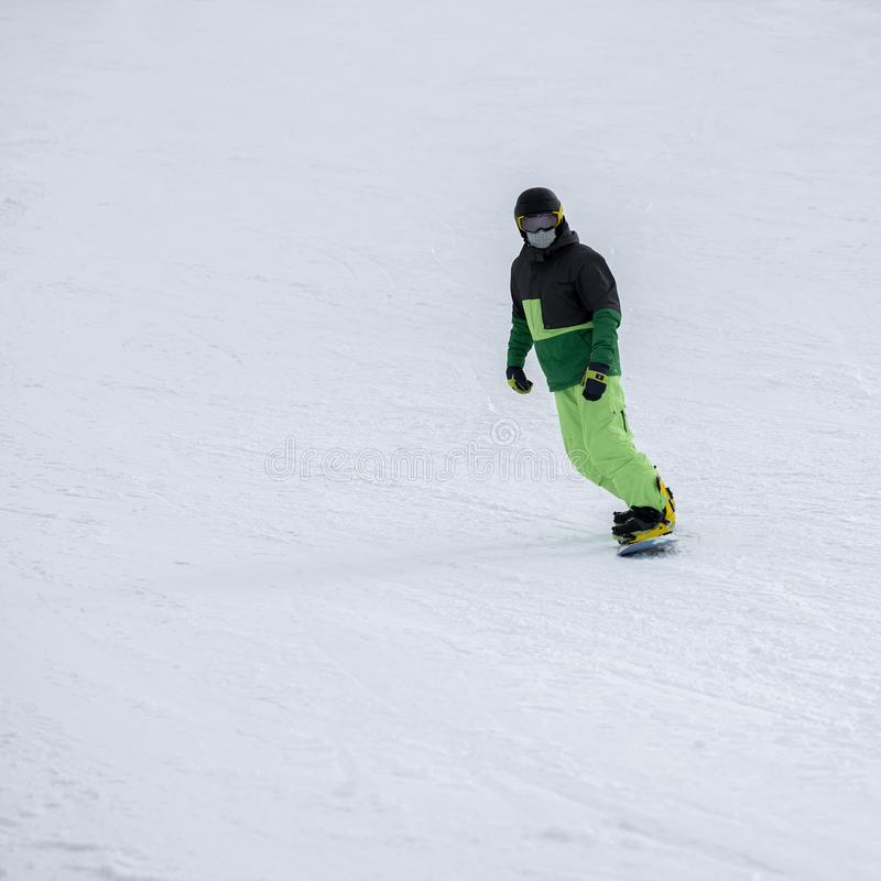 Ski méconnaissable de surfeur dans le costume lumineux, masque protecteur en verre sur la pente Sport d'hiver, surf des neiges, l image libre de droits