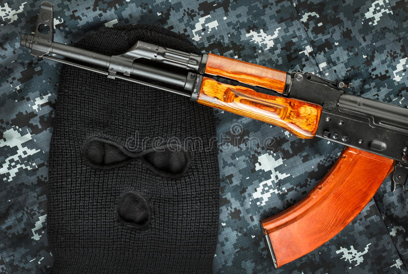 Ski mask and ak 47 on a camouflage background. Close up royalty free stock photography