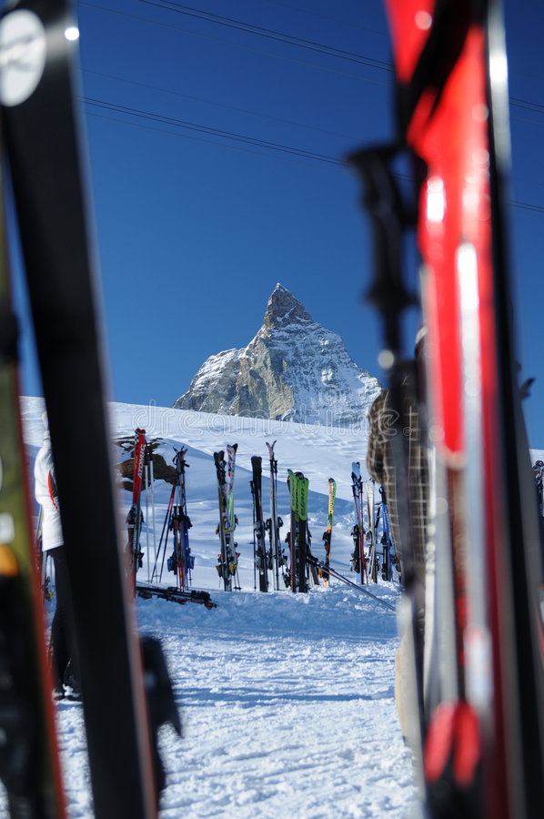 Ski at Matterhorn. Pairs of skis in the snow near a chalet. Regular ski scene near mountain chalets stock photo