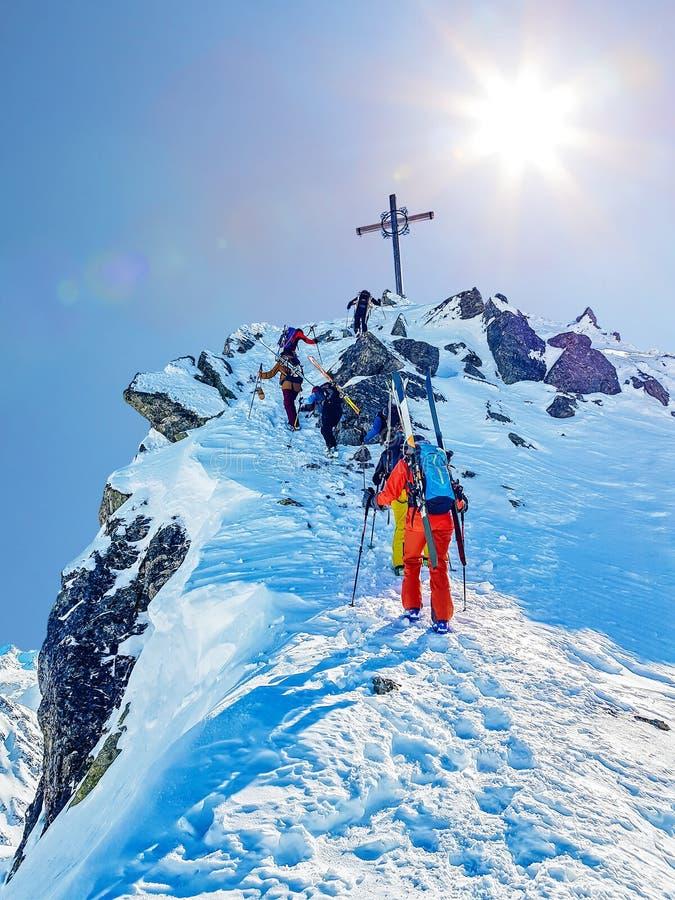 Ski mountaineering to summit cross stock photography