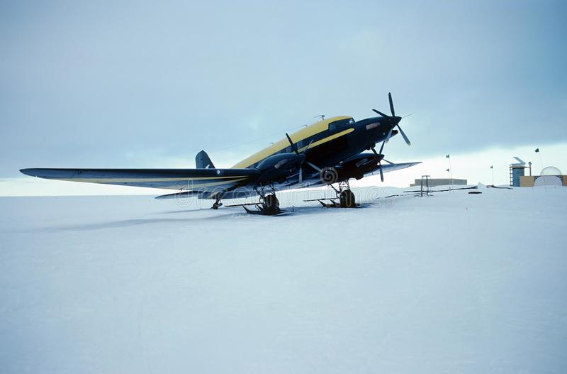 Ski plane. A ski equipped custom aircraft parked outside an Antarctic research station stock photo