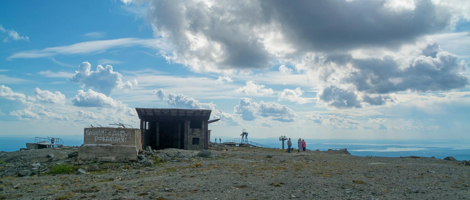 People walk along the top of the mountain Aikuivenchorr. The ski resort Bolshoy Vudyavr in Kirovsk, Russia, in the summer turns into a place for recreational stock image