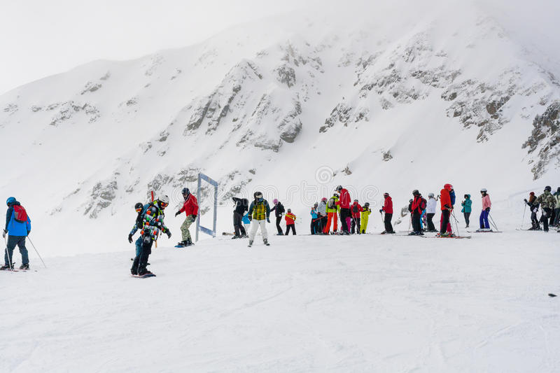 Ski resort, people at the high lift station, Bansko, Bulgaria. Bansko, Bulgaria - March 4, 2016: Ski resort, skiers at the high lift station, Bansko, Bulgaria royalty free stock images