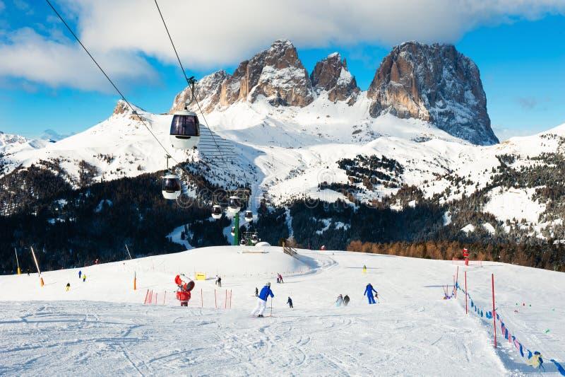 Ski resort in winter Dolomite Alps. Val Di Fassa, Italy. Ski slopes on ski resort in winter Dolomite Alps. Val Di Fassa, Italy. Skiers going down the slope royalty free stock photography
