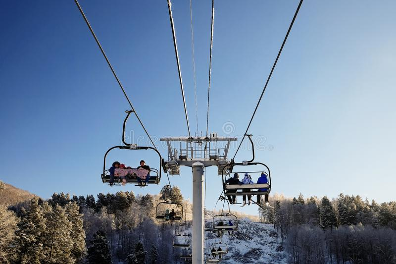 Skiërs en snouborders op sneeuwhelling in de toevlucht van de de winterski Skilift op sneeuwberg Het concept van de de winteracti stock afbeelding