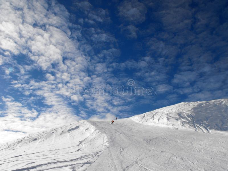 Ski slope on blue sky with clouds. stock images
