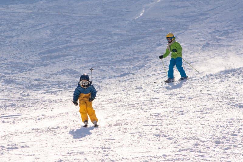 Ski, sneeuw, zon en pret met jonge geitjes op een sneeuwspoor, kind op ski stock afbeeldingen
