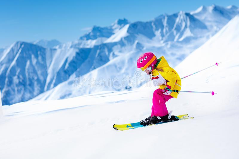 Ski and snow fun. Kids skiing. Child winter sport. Child skiing in mountains. Active toddler kid with safety helmet, goggles and poles. Ski race for young stock images