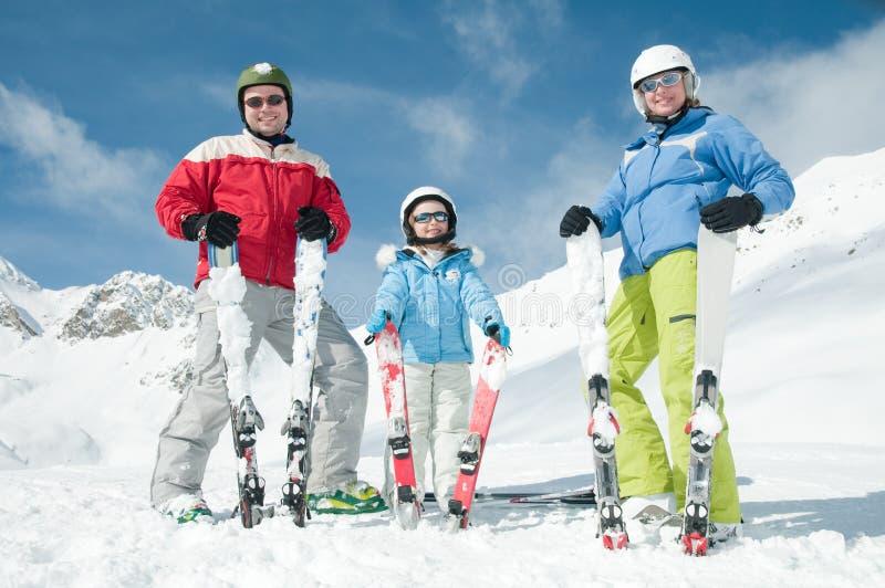 Ski, snow, sun and fun. Happy little girl with parents on ski