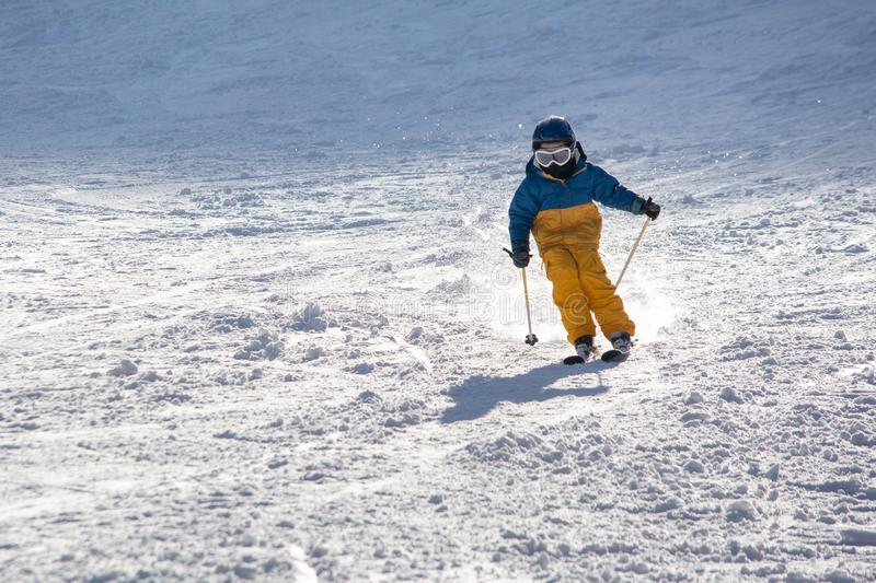 Ski, snow, sun and fun with kids on a snow track,child on ski stock photography